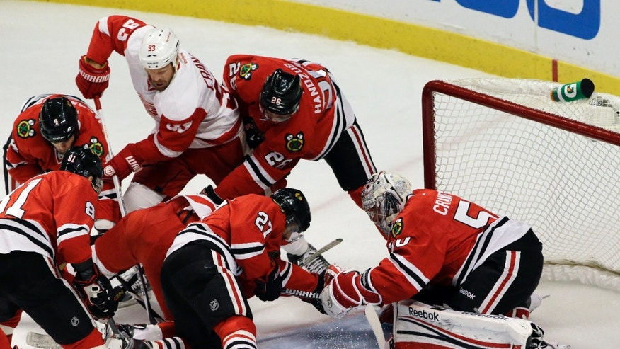 Chicago Blackhawks goalie Corey Crawford (50) saves a shot by Detroit Red Wings left wing Justin Abdelkader, obscured, during the first period in Game 7 of the NHL hockey Stanley Cup Western Conference semifinals, Wednesday, May 29, 2013, in Chicago. (AP Photo/Nam Y. Huh)