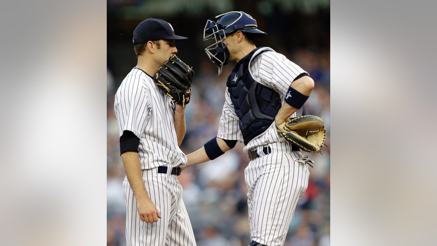 New York Yankees catcher Chris Stewart, right, talks with starting pitcher David Phelps in the first inning of in an interleague baseball game against the New York Mets at Yankee Stadium in New York, Wednesday, May 29, 2013.  Phelps allowed five runs and registered one out before manager Joe Girardi relieved him from the game. (AP Photo/Kathy Willens)