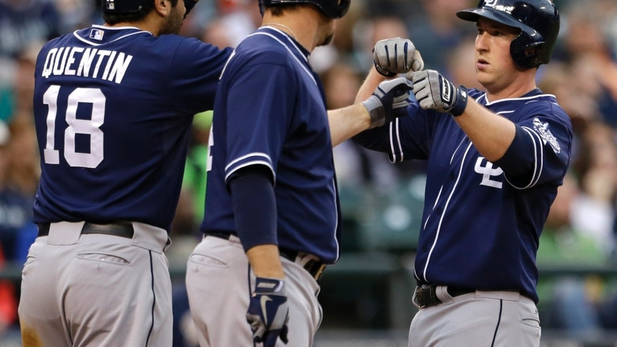 San Diego Padres' Jedd Gyorko, right, is greeted at home by Carlos Quentin (18) and Mark Kotsay after hitting a home run against the Seattle Mariners in the fourth inning of a baseball game Tuesday, May 28, 2013, in Seattle. (AP Photo/Elaine Thompson)