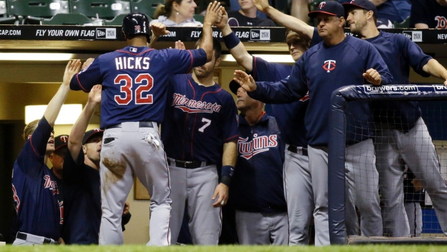Minnesota Twins' Aaron Hicks (32) is congratulated in the dugout after scoring during the 14th inning of a baseball game against the Milwaukee Brewers Tuesday, May 28, 2013, in Milwaukee. Hicks scored from third on a sacrifice fly by Eduardo Escobar. (AP Photo/Morry Gash)