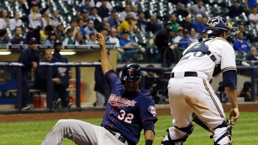 Minnesota Twins' Aaron Hicks (32) slides safely past Milwaukee Brewers catcher Jonathan Lucroy during the 14th inning of a baseball game Tuesday, May 28, 2013, in Milwaukee. Hicks scored from third on a sacrifice fly by Eduardo Escobar. (AP Photo/Morry Gash)