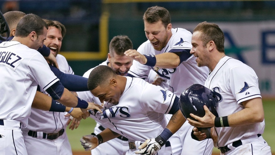 Tampa Bay Rays' Desmond Jennings, center, is mobbed by teammates, including Evan Longoria, right, Ben Zobrist, second from right, Sean Rodriguez, left, and Ryan Roberts, second from left, after his game-winning RBI single off Miami Marlins relief pitcher Chad Qualls in the ninth inning of an interleague baseball game Tuesday, May 28, 2013, in St. Petersburg, Fla. Rays' Kelly Johnson scored on the play. The Rays won 7-6. (AP Photo/Chris O'Meara)