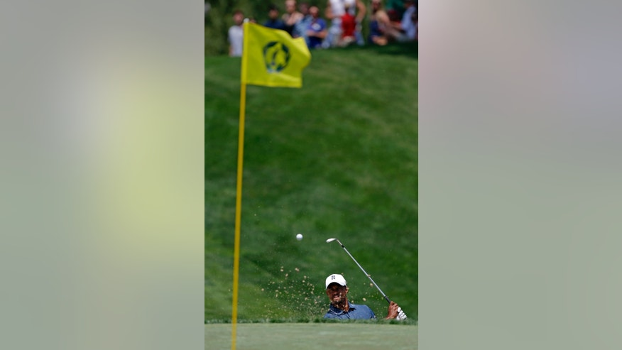 Tiger Woods hits out of a bunker on the 18th hole during the pro-am of the Memorial golf tournament  Wednesday, May 29, 2013, in Dublin, Ohio. (AP Photo/Darron Cummings)