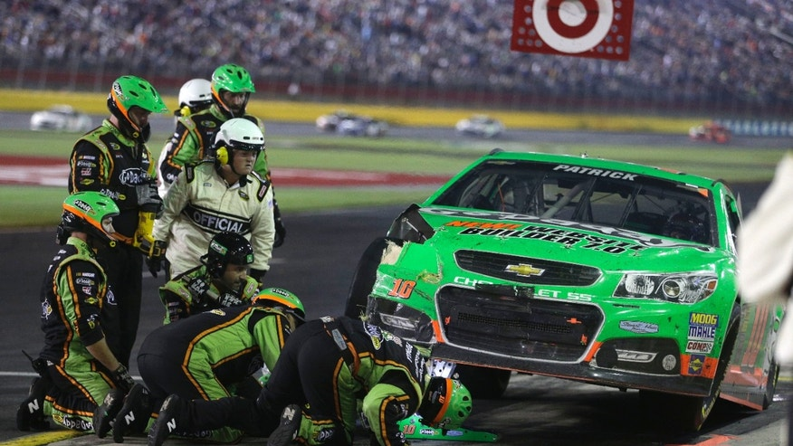 Crew members examine the damage on Danica Patrick's car after a crash during the NASCAR Sprint Cup series Coca-Cola 600 auto race at Charlotte Motor Speedway in Concord, N.C., Sunday, May 26, 2013. (AP Photo/Nell Redmond)