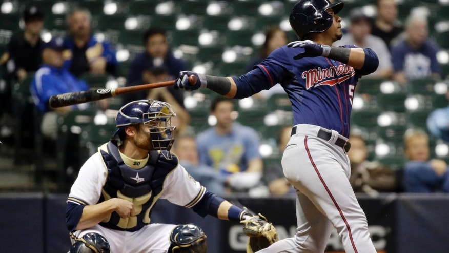 Milwaukee Brewers catcher Jonathan Lucroy watches as Minnesota Twins' Eduardo Escobar his a sacrifice fly during the 14th inning of a baseball game Tuesday, May 28, 2013, in Milwaukee. The Twins won 6-5. (AP Photo/Morry Gash)