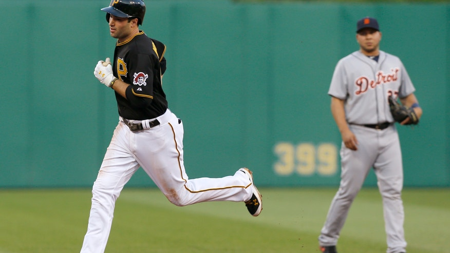 Pittsburgh Pirates' Neil Walker, left, trots past Detroit Tigers shortstop Jhonny Peralta after hitting a home run in the fourth inning of a baseball game Wednesday, May 29, 2013, in Pittsburgh. (AP Photo/Keith Srakocic)