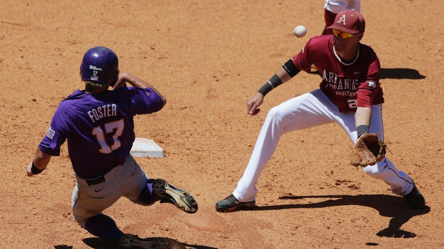 LSU's Jared Foster slides safely into second and then advances to third on a steal attempt after Arkansas second baseman Dominic Ficociello missed the throw in the seventh inning of their Southeastern Conference Tournament baseball game at the Hoover Met in Hoover, Ala., Saturday, May 25, 2013. Foster scored in the inning. (AP Photo/Dave Martin)