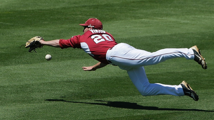 Arkansas' Matt Vinson can't make the catch on a double hit by LSU's Christian Ibarra in the seventh inning of their Southeastern Conference Tournament baseball game at the Hoover Met in Hoover, Ala., Saturday, May 25, 2013. The hit scored a run for LSU. (AP Photo/Dave Martin)