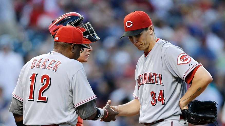Cincinnati Reds starting pitcher Homer Bailey (34) hands the ball to manager Dusty Baker (12) as he leaves in the fourth inning of a baseball game against the Cleveland Indians on Thursday, May 30, 2013, in Cleveland. Bailey gave up seven runs - all earned - in the inning. (AP Photo/Mark Duncan)
