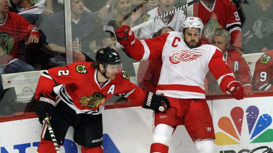 Chicago Blackhawks defenseman Duncan Keith hits Detroit Red Wings center Henrik Zetterberg during Game 7 of the NHL hockey Stanley Cup Western Conference semifinals, Wednesday, May 29, 2013, in Chicago. The Blackhawks won 2-1. (AP Photo/Daily Herald, Steve Lundy) MANDATORY CREDIT; MAGS OUT; TV OUT