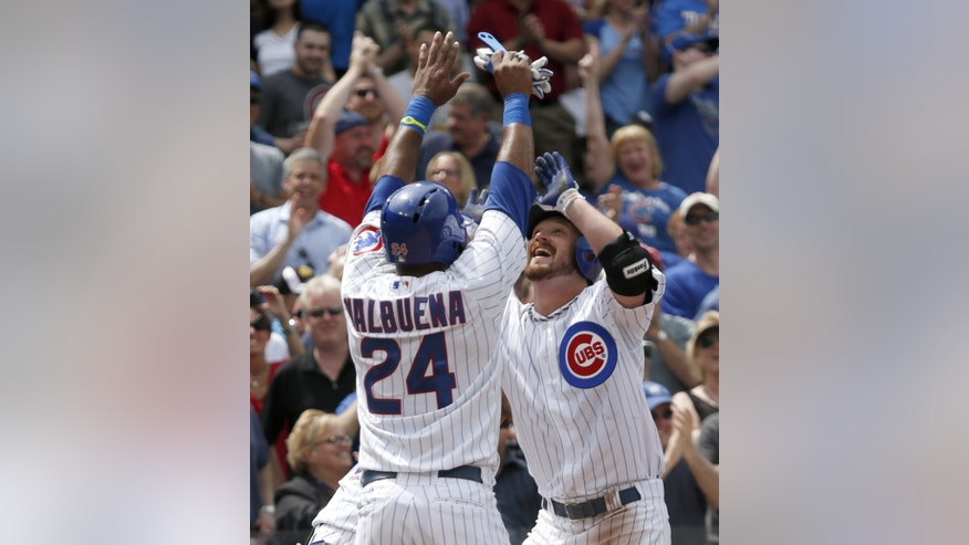 Chicago Cubs' Travis Wood, right, celebrates at home plate with Luis Valbuena after hitting a grand slam off Chicago White Sox starting pitcher Jake Peavy during the fourth inning of an interleague baseball game Thursday, May 30, 2013, in Chicago. The Cubs' Darwin Barney and Welington Castillo also scored on the hit. (AP Photo/Charles Rex Arbogast)