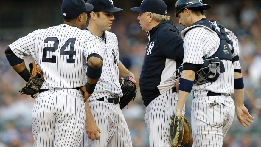 New York Yankees pitching coach Larry Rothschild, second from right, talks to starting pitcher David Phelps as second baseman Robinson Cano (24) and catcher Chris Stewart (19) listen in during the first inning of an interleague baseball game against the New York Mets at Yankee Stadium in New York, Wednesday, May 29, 2013.  Phelps allowed five runs and only recorded one out before manager Joe Girardi removed him from the game. (AP Photo/Kathy Willens)