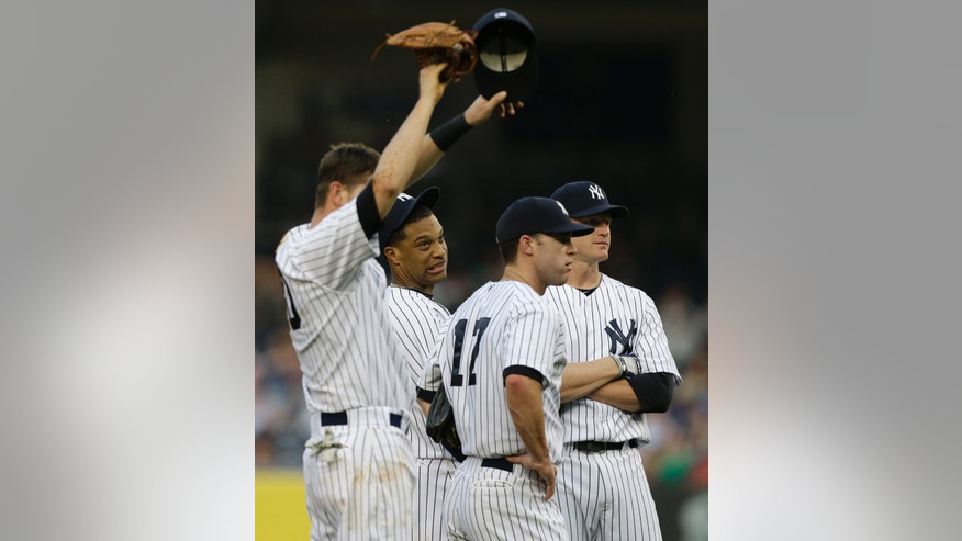 New York Yankees second baseman Robinson Cano, second from left, and teammates react after starting pitcher David Phelps allowed five runs in the first inning of an interleague baseball game against the New York Mets at Yankee Stadium in New York, Wednesday, May 29, 2013.  Yankees shortstop Reid Brignac, left, third baseman Jayson Nix (17) and first baseman Lyle Overbay look on. (AP Photo/Kathy Willens)