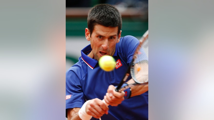 Serbia's Nonak Djokovic returns the ball to Argentina's Guido Pella during their second round match of the French Open tennis tournament at the Roland Garros stadium Thursday, May 30, 2013 in Paris. (AP Photo/Petr David Josek)