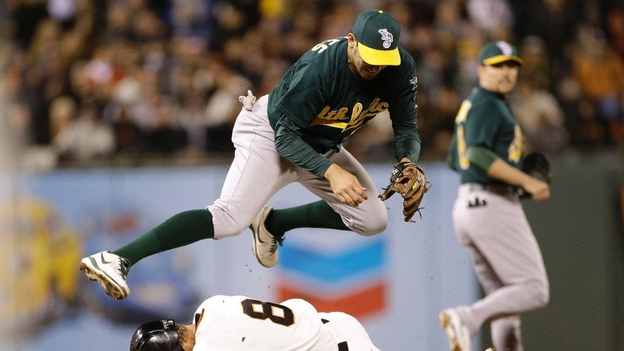 Oakland Athletics shortstop Adam Rosales tumbles over the San Francisco Giants' Hunter Pence while turning a double play in the ninth inning of their baseball game Wednesday, May 29, 2013 in San Francisco. Oakland won 9-6. (AP Photo/Eric Risberg)