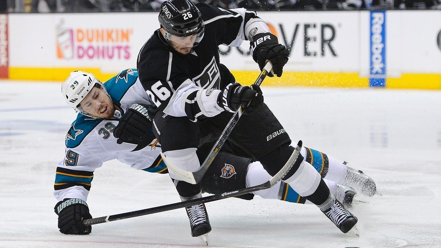 Los Angeles Kings defenseman Slava Voynov, foreground, of Russia takes the puck away form San Jose Sharks center Logan Couture during the first period in Game 7 of the Western Conference semifinals in the NHL hockey Stanley Cup playoffs, Tuesday, May 28, 2013, in Los Angeles.  (AP Photo/Mark J. Terrill)