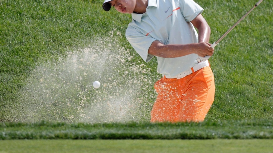 Amateur Guan Tianlang, of China, hits from the sand on the ninth hole during the first round of the Memorial golf tournament Thursday, May 30, 2013, in Dublin, Ohio. (AP Photo/Jay LaPrete)