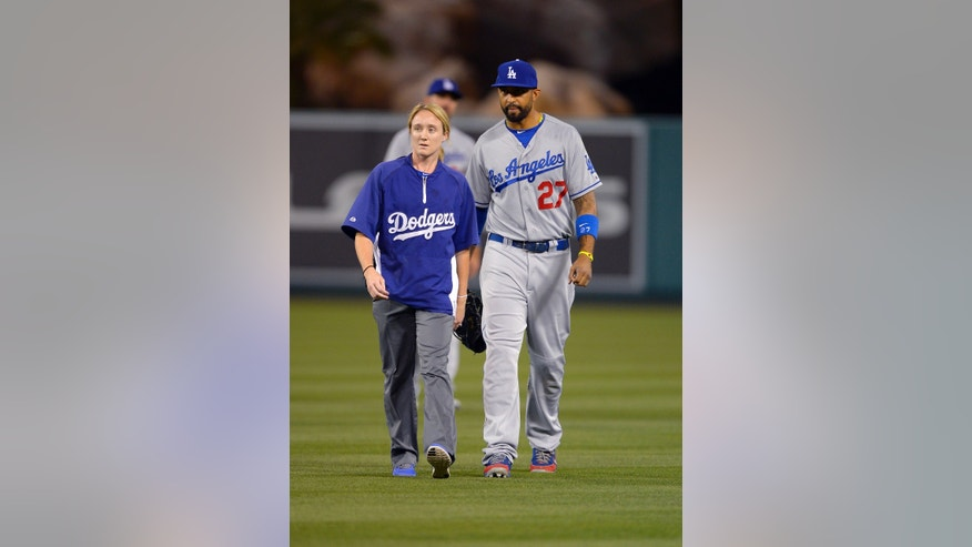 Los Angeles Dodgers center fielder Matt Kemp, right, walks off the field with trainer Sue Falsone during the seventh inning of their baseball game against the Los Angeles Angels, Wednesday, May 29, 2013, in Anaheim, Calif. The Angels won 4-3. (AP Photo/Mark J. Terrill)