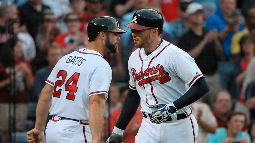 Atlanta Braves' Freddie Freeman is congratulated by teammate Evan Gattis (24) after Freeman's home run against the Toronto Blue Jays in the third inning of a baseball game at Turner Field in Atlanta, Thursday, May 30, 2013. (AP Photo/David Tulis)