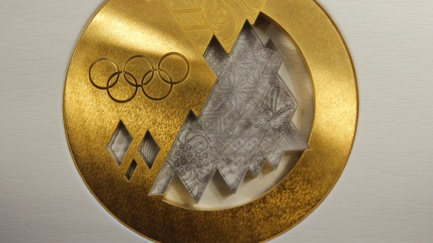 The gold medal is displayed for journalists during a presentation of Sochi 2014 Olympic medals at the SportAccord International Convention in St. Petersburg, Russia, Thursday, May 30, 2013. (AP Photo/Dmitry Lovetsky)