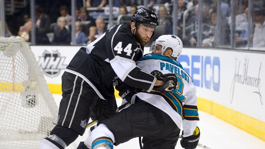 Los Angeles Kings defenseman Robyn Regehr, left, pushes San Jose Sharks center Joe Pavelski off the puck during the third period in Game 7 of the Western Conference semifinals in the NHL hockey Stanley Cup playoffs, Tuesday, May 28, 2013, in Los Angeles.  (AP Photo/Mark J. Terrill)