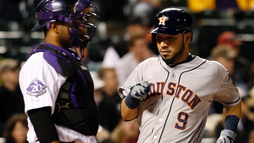 Houston Astros' Marwin Gonzalez, right, crosses home plate to score the go-ahead run on a single by J.D. Martinez as Colorado Rockies catcher Wilin Rosario looks on in the eighth inning of the Astros' 6-3 victory in a baseball game in Denver on Wednesday, May 29, 2013. (AP Photo/David Zalubowski)