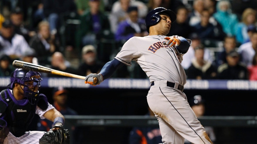 Houston Astros' Carlos Pena, right, follows the flight of his solo home run with Colorado Rockies cather Wilin Rosario to lead off the in the ninth inning of the Astros' 6-3 victory in a baseball game in Denver on Wednesday, May 29, 2013. (AP Photo/David Zalubowski)