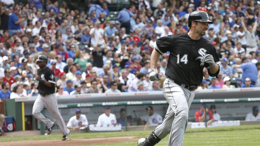 Chicago White Sox's Paul Konerko (14) heads to first after hitting an RBI single off Chicago Cubs starting pitcher Travis Wood, scoring Alejandro De Aza, left, during the third inning of an interleague baseball game Thursday, May 30, 2013, in Chicago. (AP Photo/Charles Rex Arbogast)