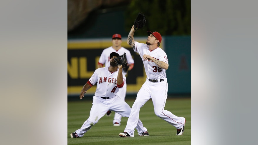 Los Angeles Angels right fielder Josh Hamilton, right, and second baseman Howie Kendrick look to catch a ball hit by Los Angeles Dodgers' Mark Ellis during the eighth inning of a baseball game in Anaheim, Calif., Thursday, May 30, 2013. (AP Photo/Jae C. Hong)