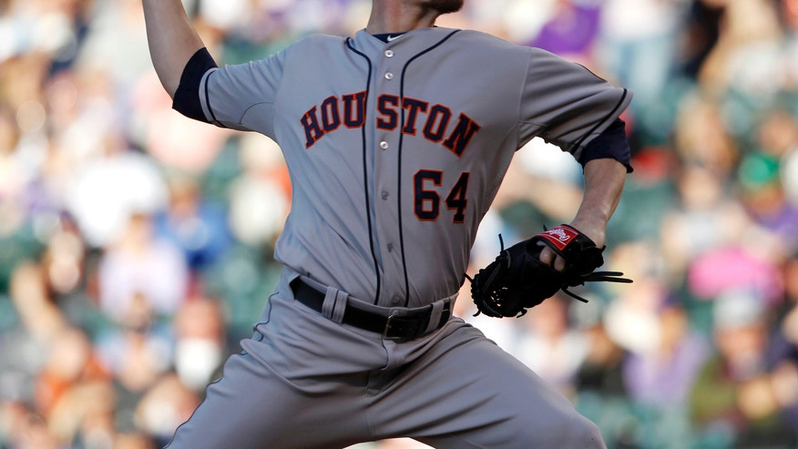 Houston Astros starting pitcher Lucas Harrell works against the Colorado Rockies in the first inning of a baseball game in Denver, Thursday, May 30, 2013. (AP Photo/David Zalubowski)