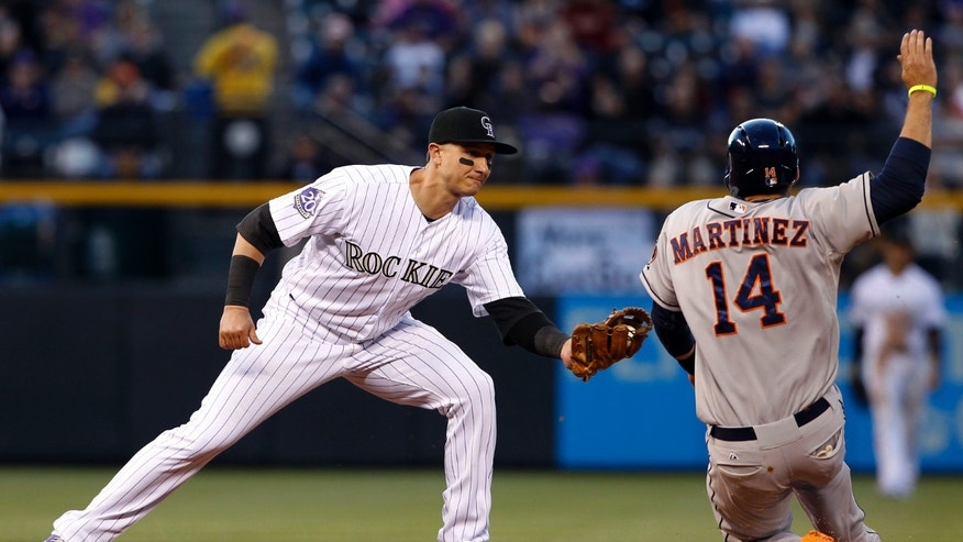 Colorado Rockies shortstop Troy Tulowitzki, left, tags out Houston Astros' J.D. Martinez at second base on the back end of a double play hit into by Carlos Pena in the fourth inning of a baseball game in Denver, Thursday, May 30, 2013. (AP Photo/David Zalubowski)
