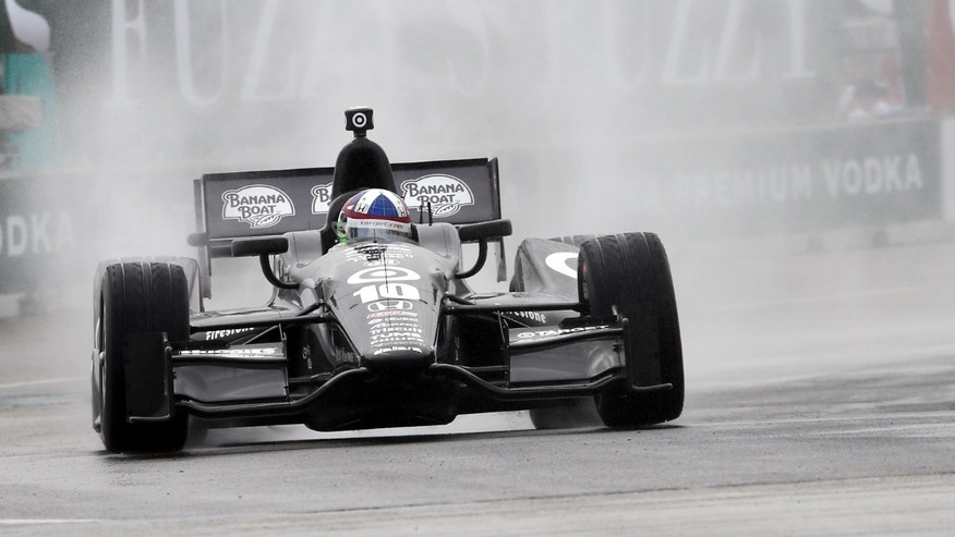 Water sprays from the rear wheels as IndyCar driver Dario Franchitti takes turn two during qualifying for this weekend's Detroit Grand Prix auto race on Belle Isle in Detroit, Friday, May 31, 2013. (AP Photo/Bob Brodbeck)