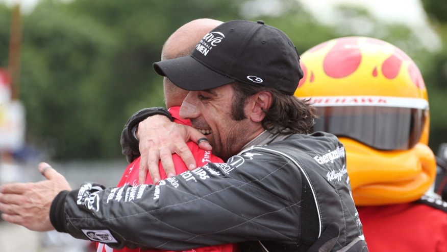 IndyCar driver Dario Franchitti hugs a team member after qualifying for the pole position for Saturday's Race 1 of the Detroit Grand Prix auto races on Belle Isle in Detroit, Friday, May 31, 2013. The second race of the Detroit Duel is on Sunday. (AP Photo/Bob Brodbeck)