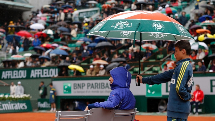 Serbia's Nonak Djokovic sits under an umbrella during a rainfall as he plays Argentina's Guido Pella during their second round match of the French Open tennis tournament at the Roland Garros stadium Thursday, May 30, 2013 in Paris. (AP Photo/Petr David Josek)