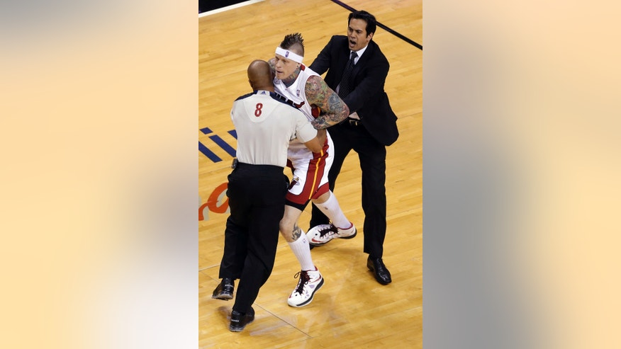 Official Marc Davis (8) and Miami Heat coach Erik Spoelstra restrain Heat's Chris Andersen during the first half of Game 5 in the NBA basketball playoffs Eastern Conference finals, Thursday, May 30, 2013, in Miami. Andersen was charged with a flagrant foul. (AP Photo/Wilfredo Lee)