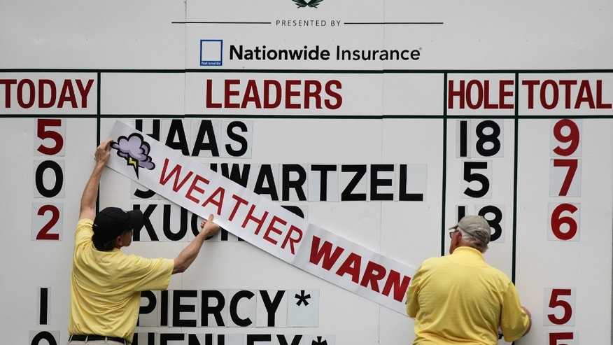 Volunteers hang a weather warning sign on a leaderboard after play was suspended during the second round of the Memorial golf tournament Friday, May 31, 2013, in Dublin, Ohio. (AP Photo/Jay LaPrete)