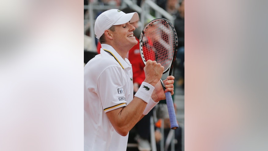John Isner of the U.S. celebrates defeating compatriot Ryan Harrison in five sets in their second round match at the French Open tennis tournament, at Roland Garros stadium in Paris, Friday, May 31, 2013. (AP Photo/Christophe Ena)