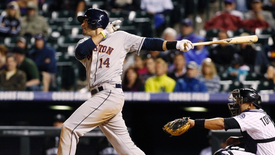 Houston Astros' J.D. Martinez, left, follows the flight of his single along with Colorado Rockies catcher Yorvit Torrealba in the ninth inning of the Astros' 7-5 victory in a baseball game in Denver on Thursday, May 30, 2013. (AP Photo/David Zalubowski)