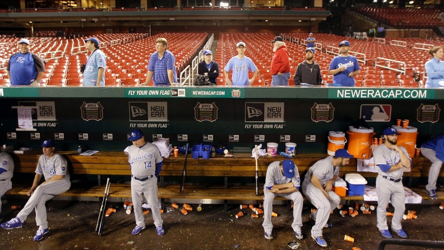 Members of the Kansas City Royals wait along with a few fans for the restart of a baseball game during a rain delay during the ninth inning against the St. Louis Cardinals Friday, May 31, 2013, in St. Louis. The game finally ended after 3 a.m. CDT, with a 4-2 Royals victory. (AP Photo/Jeff Roberson)