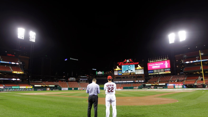 St. Louis Cardinals manager Mike Matheny, right, and general manager John Mozeliak look out over a rain-soaked field after the tarp was pulled away during a rain delay in the ninth inning a baseball game against the Kansas City Royals Friday, May 31, 2013, in St. Louis. The delay started after the Royals took the lead in the ninth inning Thursday evening. (AP Photo/Jeff Roberson)