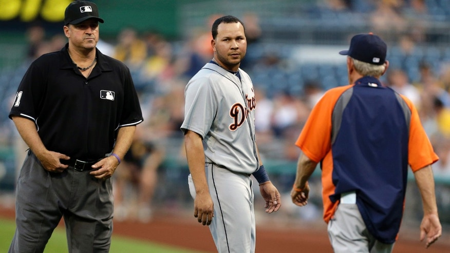 Detroit Tigers' Jhonny Peralta, center, walks to the dugout past first base umpire Tony Randazzo, left, as Tigers manager Jim Leyland heads out for a explanation after home plate umpire Manny Gonzalez ejected Peralta from the game for complaining about a called third strike in the fourth inning of a baseball game against the Pittsburgh Pirates in Pittsburgh, Thursday, May 30, 2013. (AP Photo/Gene J. Puskar)