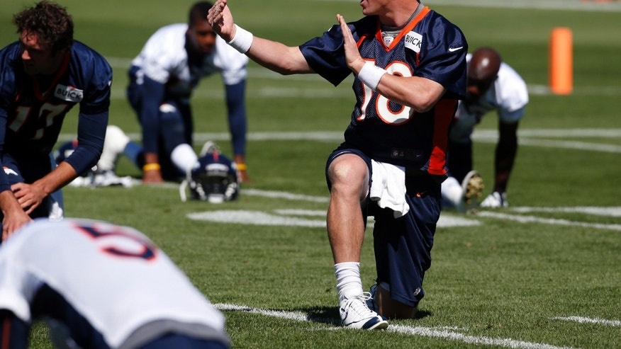 Denver Broncos quarterback Peyton Manning (18) talks to teammates during stretching at off season training camp at the NFL football team's training facility in Englewood, Colo., on Thursday, May 30, 2013. (AP Photo/Ed Andrieski)
