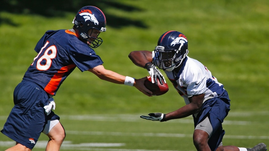 Denver Broncos quarterback Peyton Manning, left, hands the ball off to running back Montee Ball during NFL football team's training facility in Englewood, Colo., on Thursday, May 30, 2013. (AP Photo/Ed Andrieski)