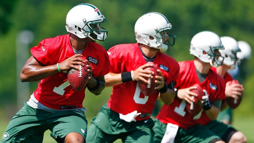 New York Jets quarterbacks Geno Smith (7), Mark Sanchez (6), Greg McElroy (14) and Matt Simms (5) drop back to pass during a drill at NFL football practice in Florham Park, N.J., Thursday, May 30, 2013. (AP Photo/Rich Schultz)