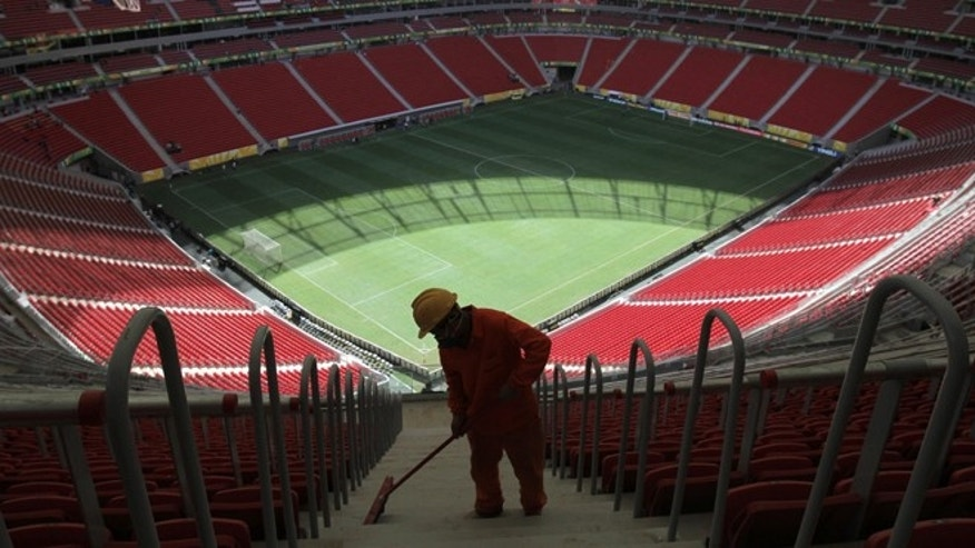 A worker cleans the stairs of the Mane Garrincha National Stadium before the training session of the Brazilian team in Brasilia, Brazil, Friday, June 14, 2013. Brazil will face Japan in the opening match of the soccer Confederations Cup on June 15. (AP Photo/Eraldo Peres)
