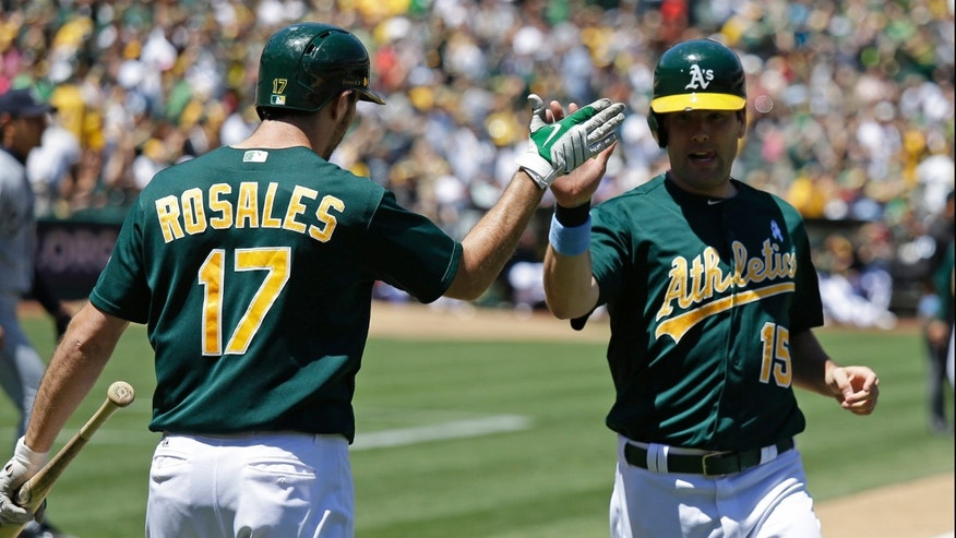 Oakland Athletics' Seth Smith, right, is greeted by teammate Adam Rosales, left, after scoring the A's second run in the fourth inning of their baseball game against the Seattle Mariners Sunday, June 16, 2013 in Oakland, Calif. (AP Photo/Eric Risberg)