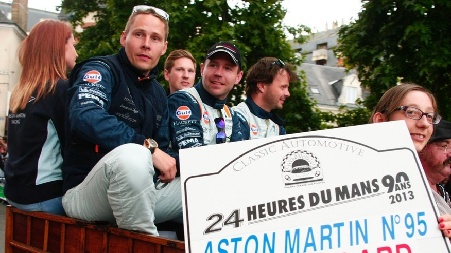 "Danish Driver Allan Simonsen, left, is seen during a parade on the eve of the 90th 24-hour Le Mans endurance race, in Le Mans, western France.. The No.95 Aston Martin Vantage GTE, driven by Simonsen, exited the track at high speed at the ""Tertre Rouge"" corner on his fourth lap of the race. He died after due to his injuries."