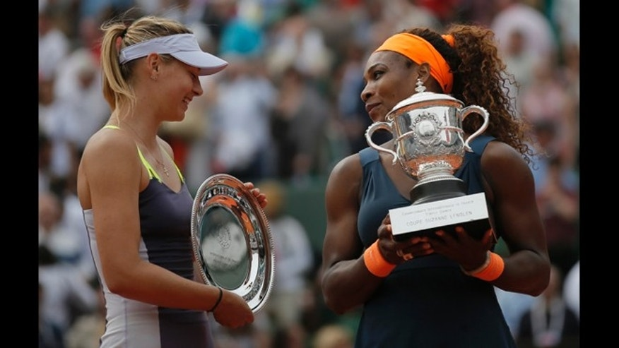 June 8, 2013: Serena Williams of the U.S., right, holds the trophy after defeating Russia's Maria Sharapova, left, in two sets 6-4, 6-4, in the women's final of the French Open tennis tournament, at Roland Garros stadium in Paris.
