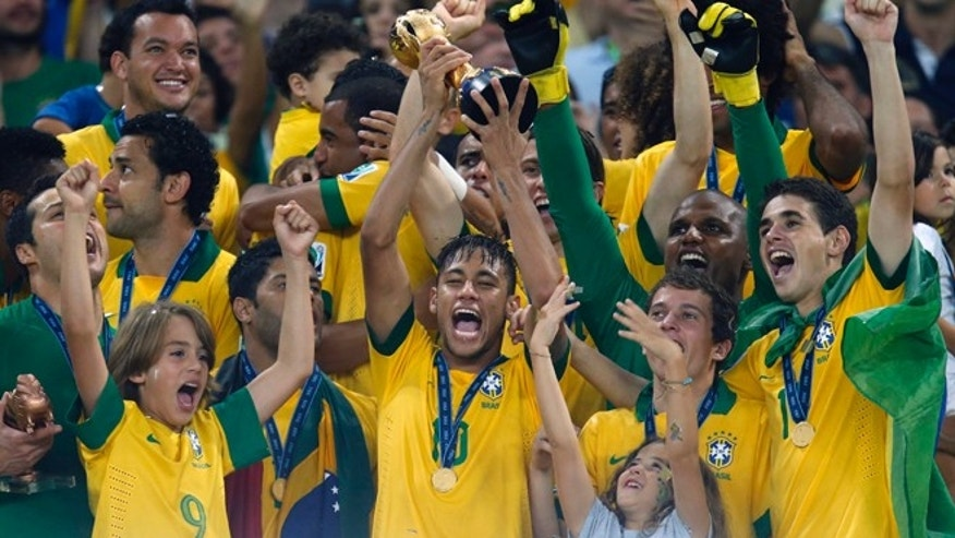 Brazil's Neymar, center, lifts the trophy after winning the soccer Confederations Cup final between Brazil and Spain at the Maracana stadium in Rio de Janeiro, Brazil, Sunday, June 30, 2013. (AP Photo/Victor Caivano)