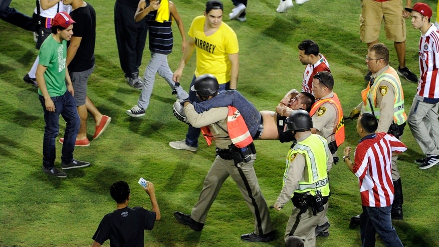 Police carry off a fan from the field after Chivas defeated Club America 1-0 at the El Super Clasico soccer match on Wednesday, July 3, 2013 in Las Vegas. (AP Photo/David Becker)
